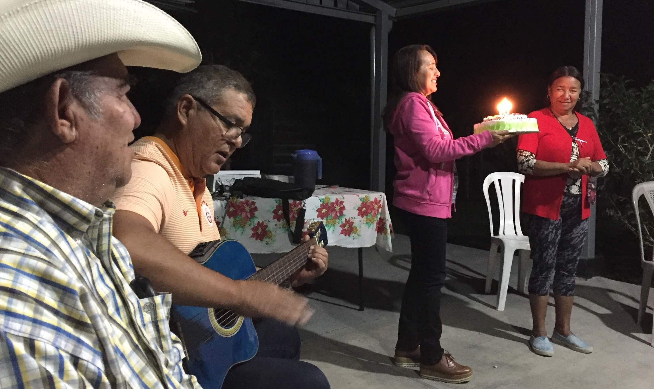 In a PSE group in Santa Rosa de Lima, Cesar looks on as Humberto plays a birthday song on his guitar while his wife Enma brings out a birthday cake for a member of their group.