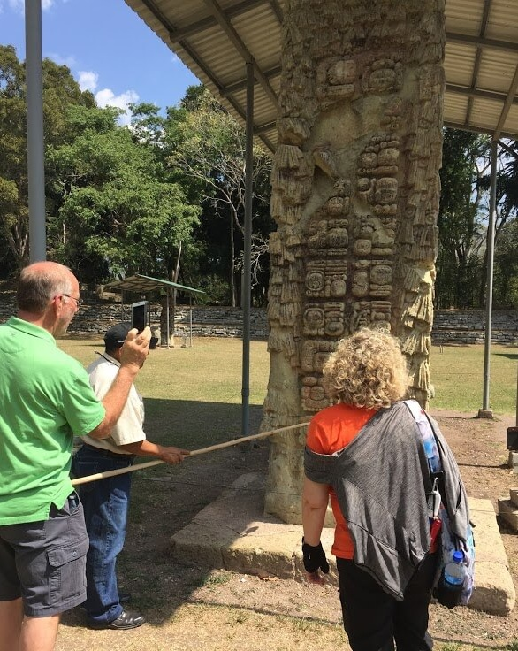 Nola and Rex listen to the guide tell how this stella chronicles the history of one of the Mayan kings.