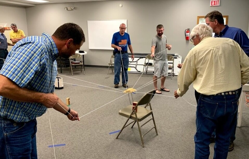 In the PSE training, participants play using Marty's game. The goal is to move blocks to designated spots in the circle.
