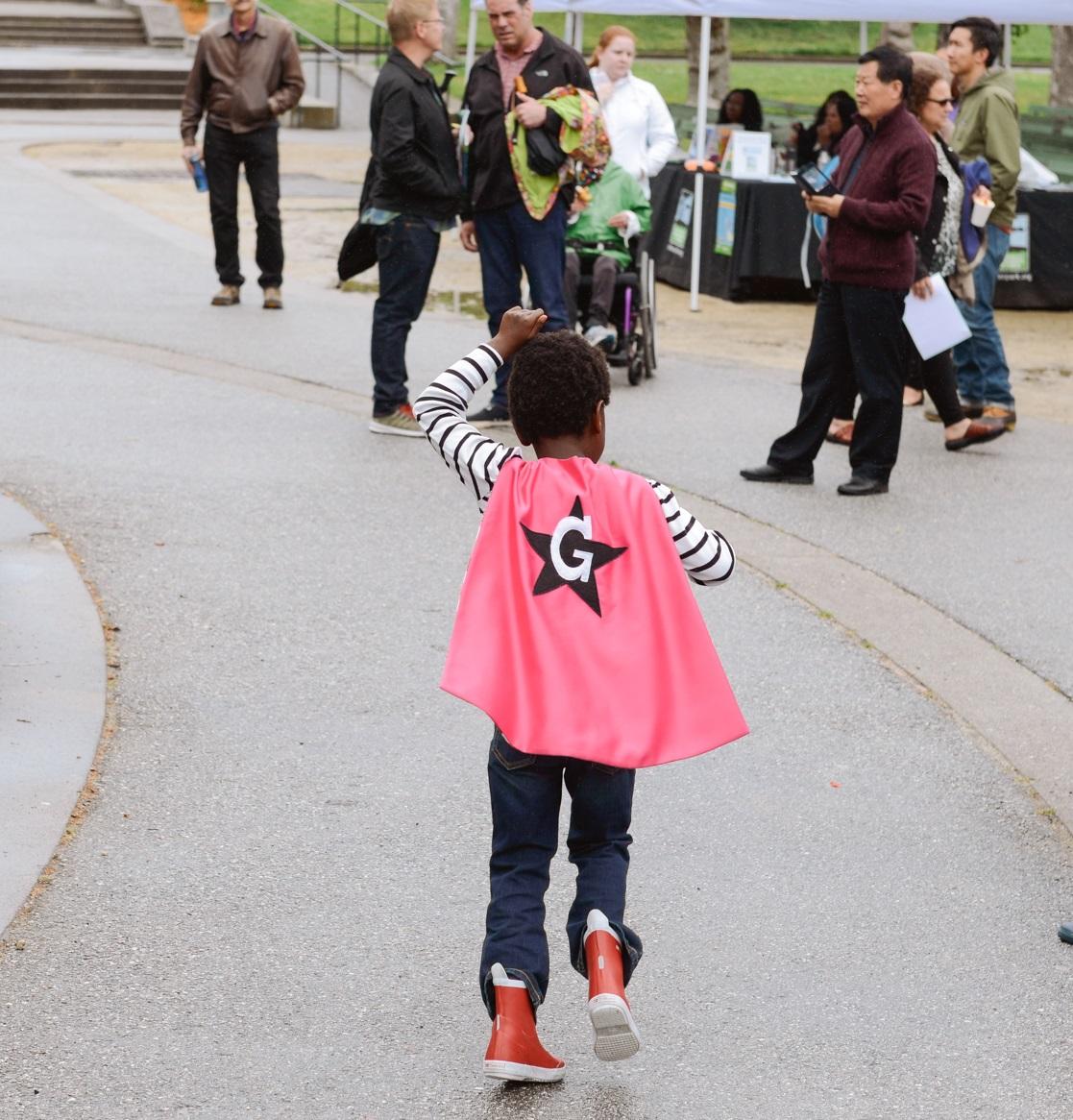 Girl running through Golden Gate Park in a pink cape