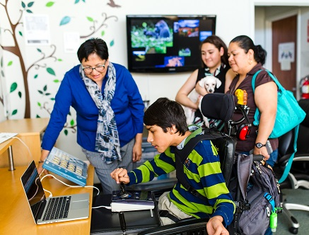 Family watching young man use Assistive Technology Equipment at Support for Families