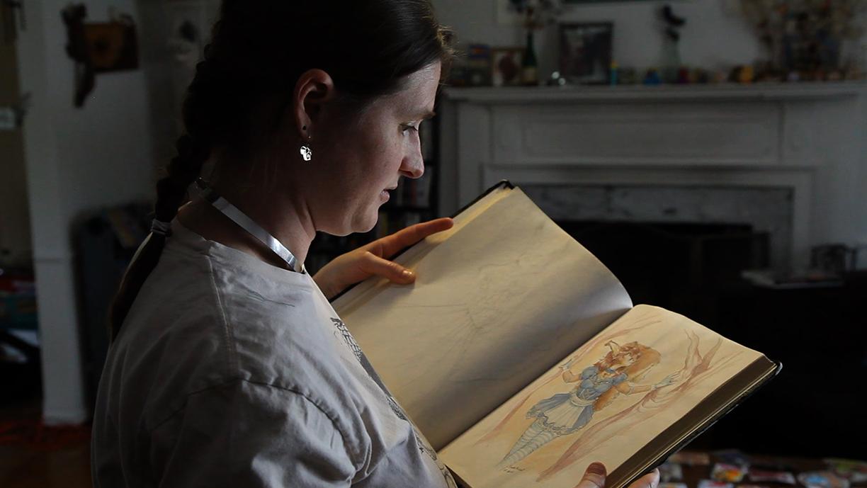 Mystee flips through a book of artwork