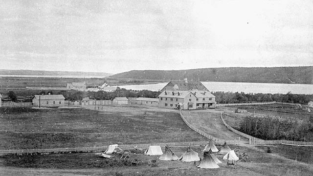 A10:   Fort Qu'Appelle Indian Residential School, distant view with tents, carts and teepees at the fence perimetre, Lebret, [May 1885?]