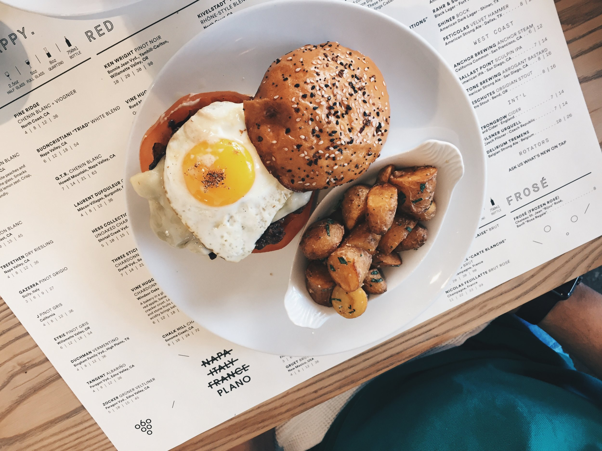 The C.A.B. Brunch Burger - cabernet smothered local akaushi patty, sunny free range egg, everything bun, raclette cheese, caramelized onions, worcestershire mayo, tomato. duck fat breakfast potatoes