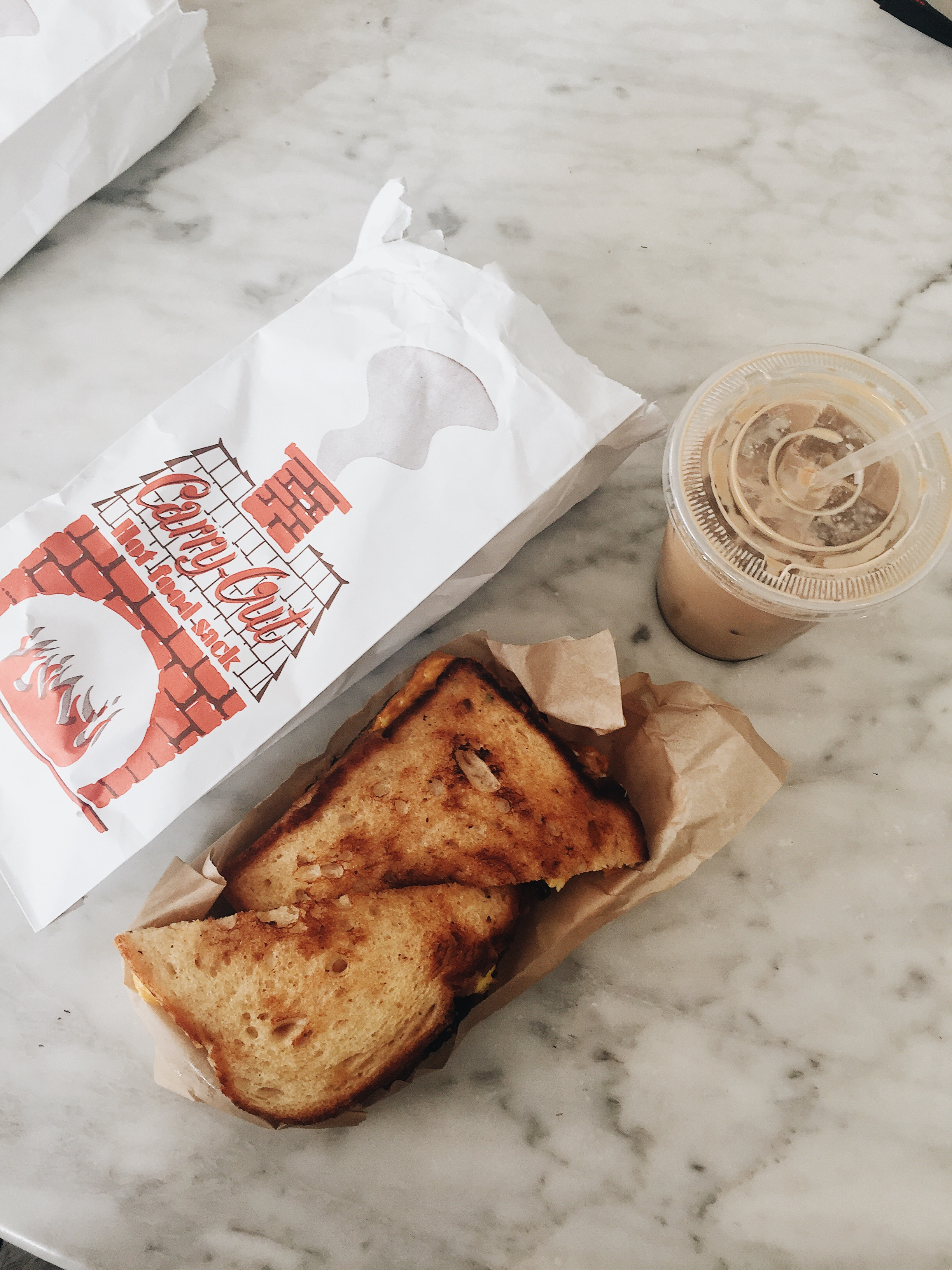 Breakfast - Breakfast sandwich with bacon and an iced cafe latte.