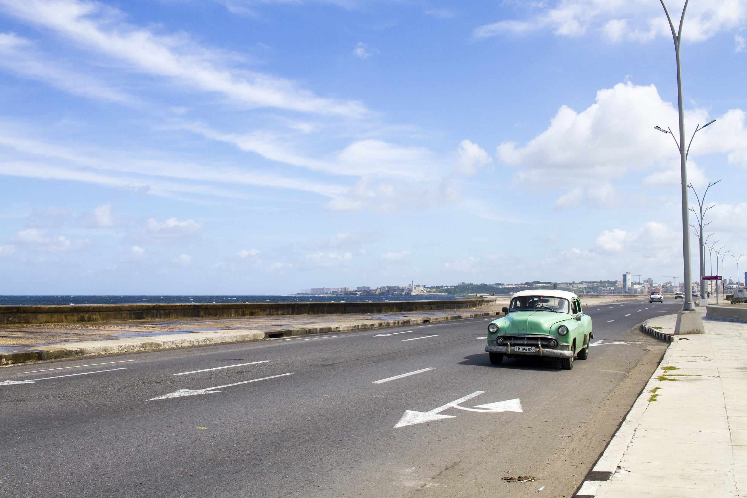 A restored classic car driving down the Malecón in La Habana