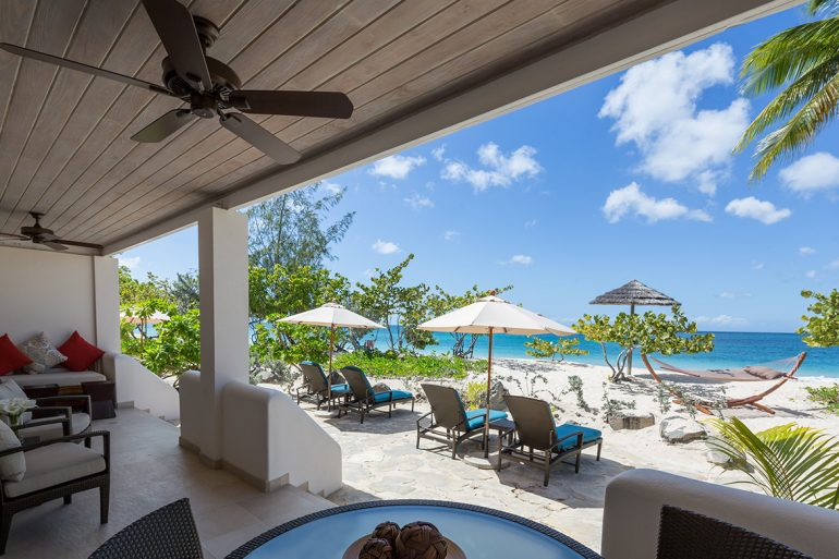 Caribbean Living Magazine - Peaking out from the rocky cliffs overlooking the brilliant azure waters of Boston Bay, lies Great Huts, Paradise on the Edge.