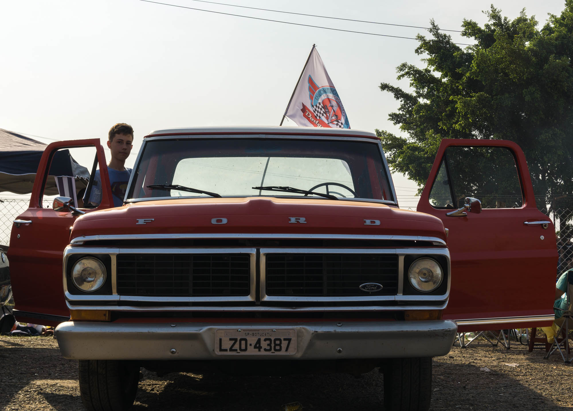 Boy Gets into Classic Red Ford Pickup Truck