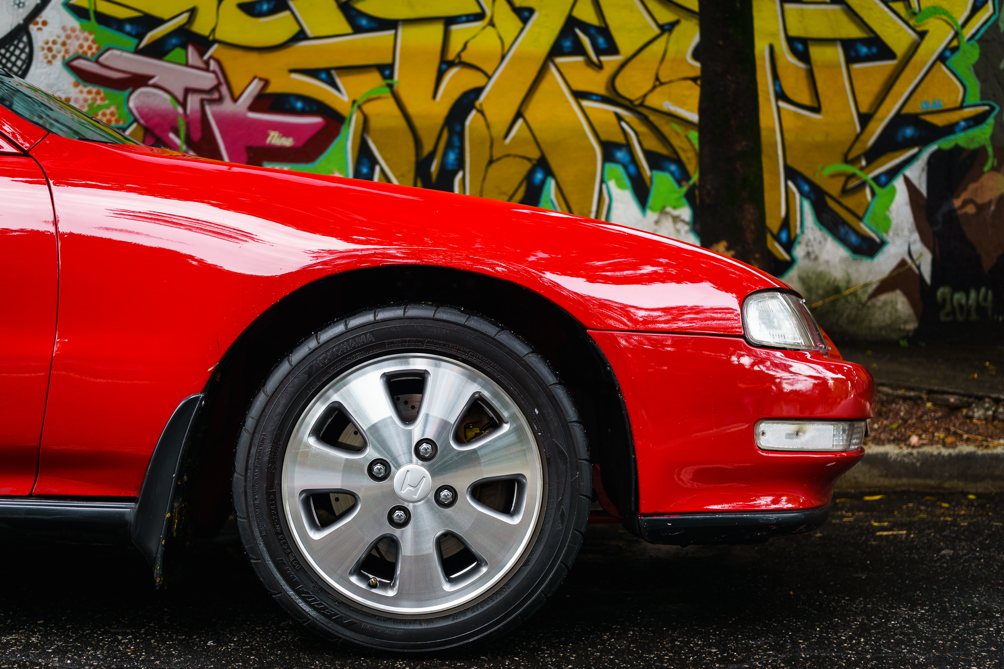 Front Wheel of a Prelude in front of Graffiti