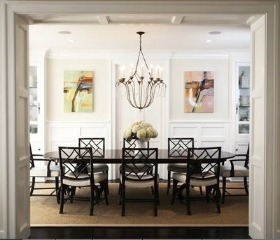 Contrast can happen with style, too. This traditional dining room has plenty of architectural details already, but the modern paintings hung in a row add an interesting rhythmical contrast.