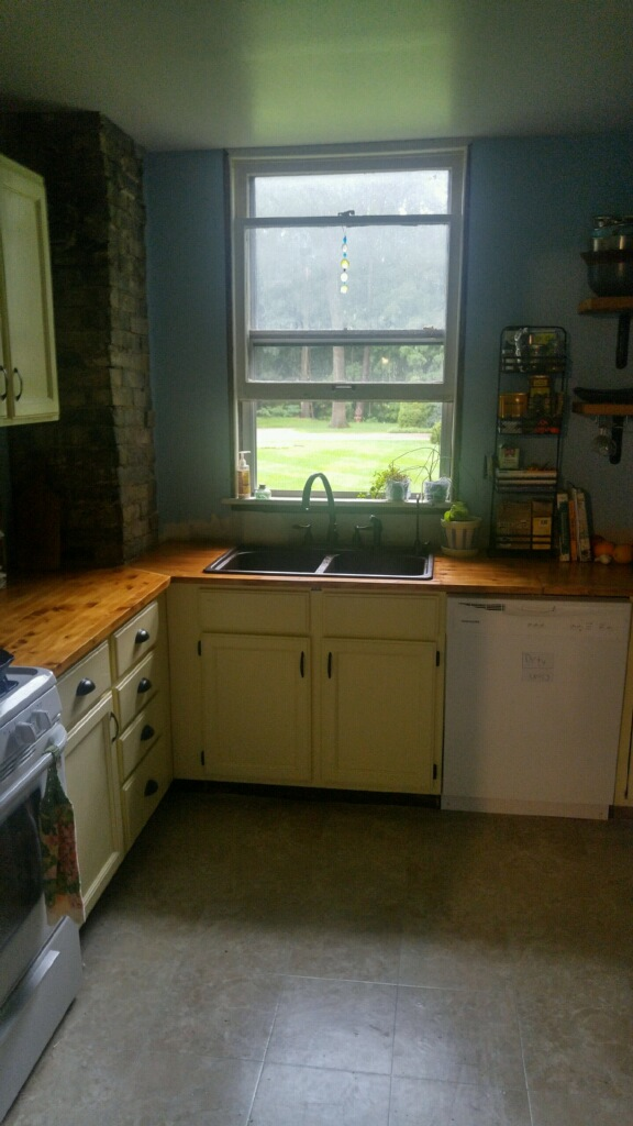 This is the view of the kitchen when you are in the dining room.  She completely redid the kitchen herself.  New (to her) cabinets, new wood counter tops, new flooring, and open shelving.  It's a a very peaceful and light-filled room.