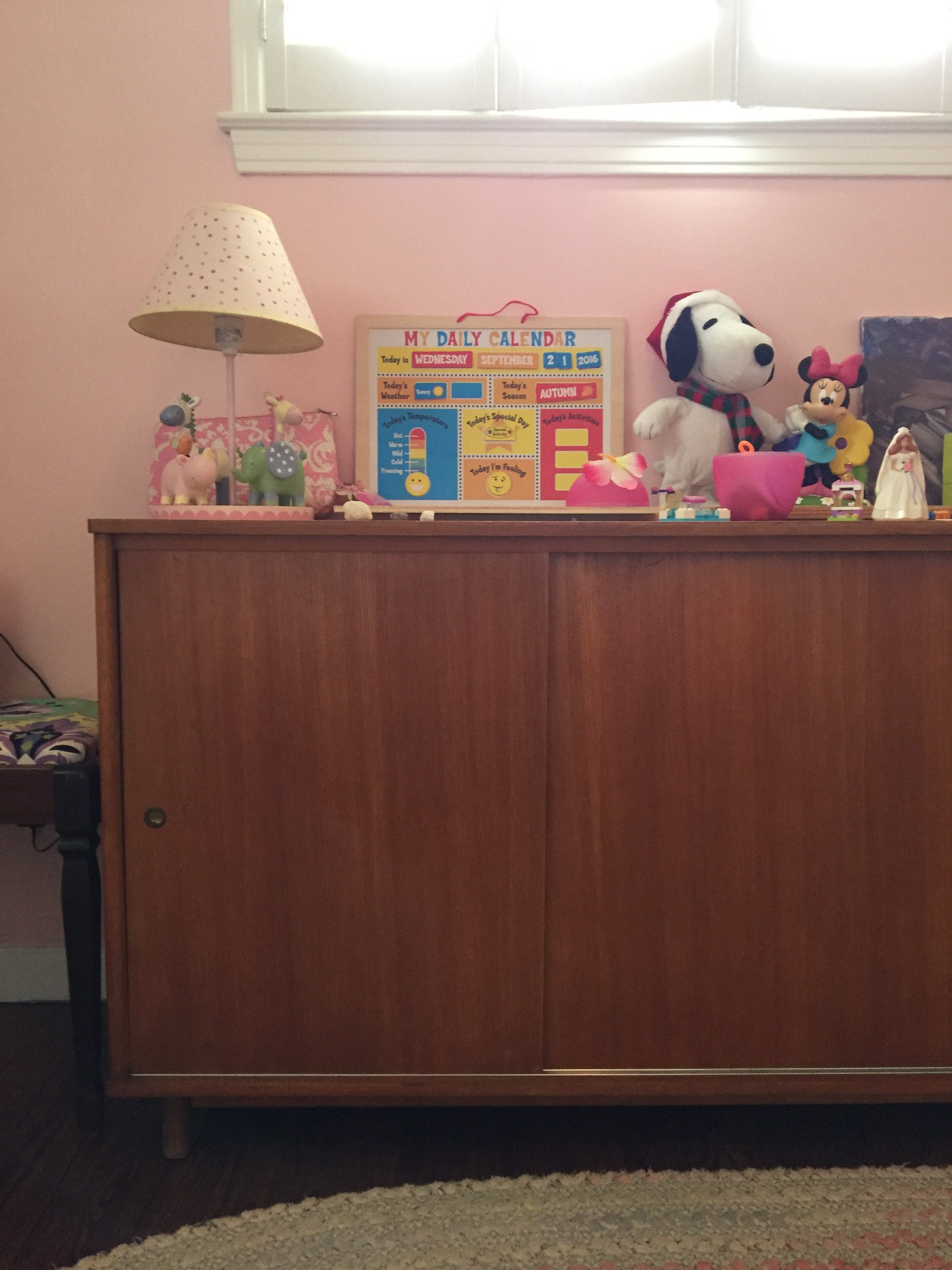 On the wall next to that stool/bench is a vintage teak credenza by Drexel.  Everything on top is within reach to Meena, and she only uses the top of the credenza to store more toys and knick/knacks.  The inside of the credenza is full of my crafting supplies.