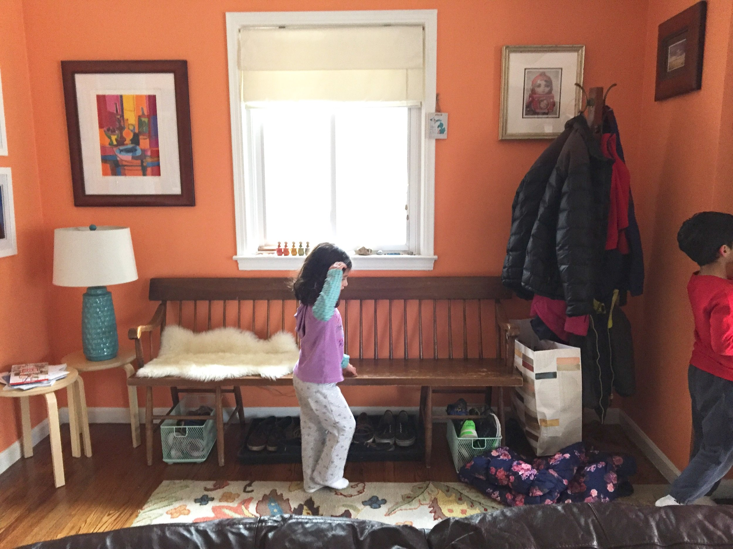 "Meena throws her coat on the floor. I say, ""Please hang up your coat on the rack"". Meena looks at it."