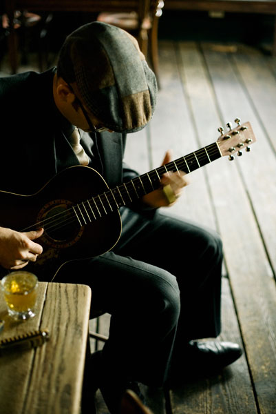 The Milkman & Sons -Marcus on guitar with whiskey.jpg