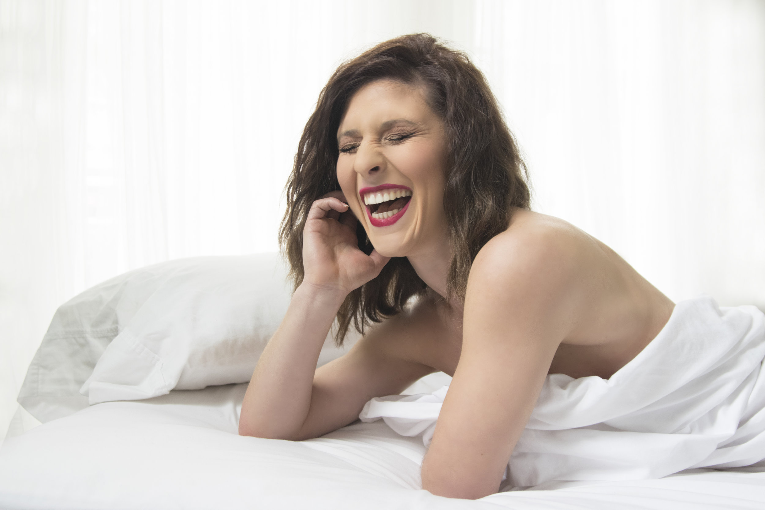 Portrait of a woman laughing in bed