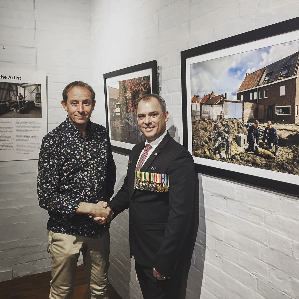 Artist Ian Alderman (left) and Jason Scanes - the Queensland government's Anzac100 representative - are pictured at the exhibition opening event