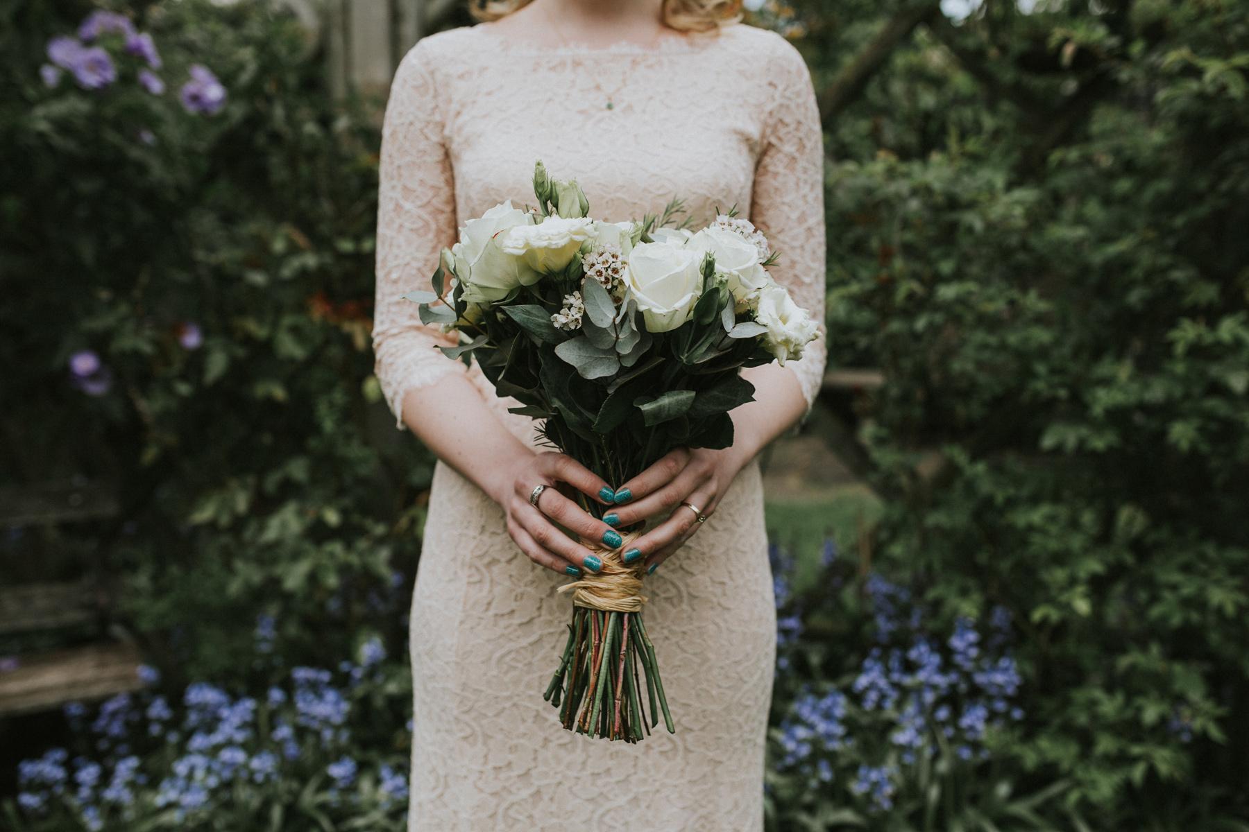 alternative Bride holding white rose bouquet blush lace Diane Von Furstenberg wedding dress Clapham London