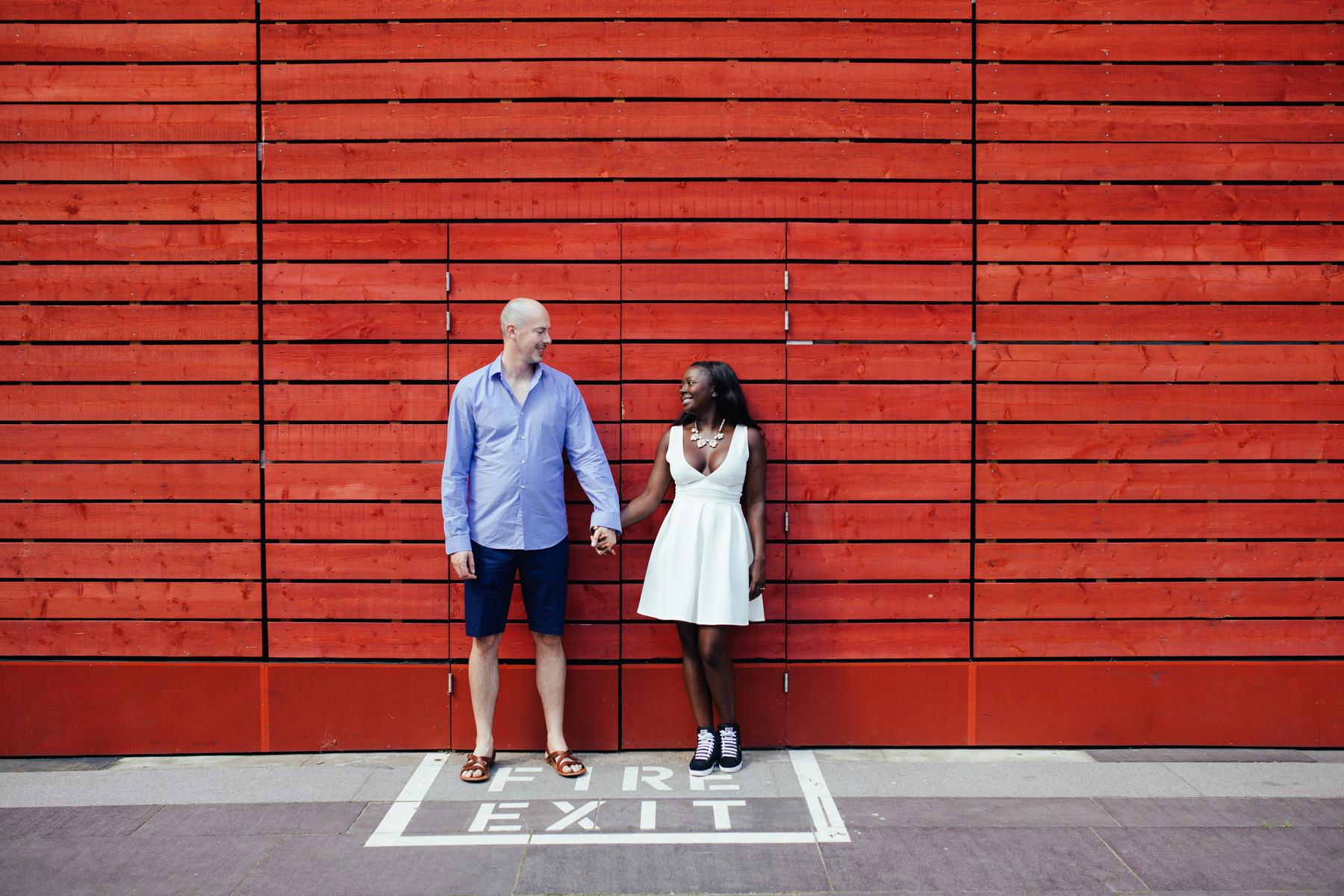 London-alternative-wedding-Southbank-engagement-photographer-couple-against-red-background