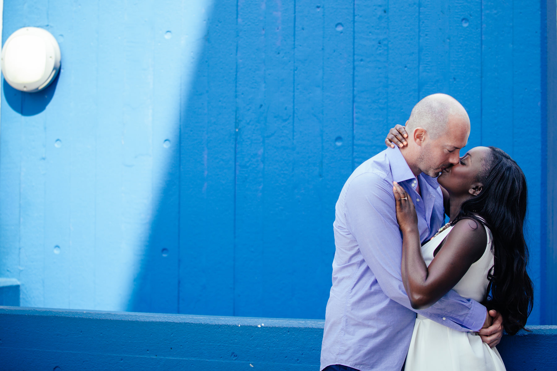 London-Southbank-engagement-photographer-engaged-couple-standing-against-blue-wall