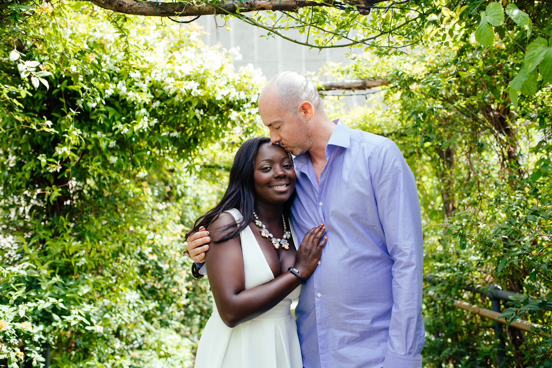 London-engagement-photographer-couple-standing-under-vines-secret-garden-bar-Southbank