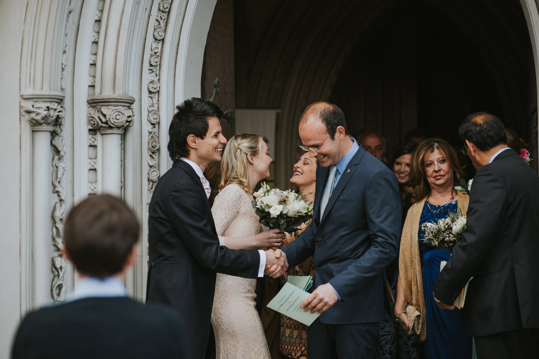 LD-306-groom--bride-greeting-guests-St-Marys-catholic-church-wedding-London.jpg