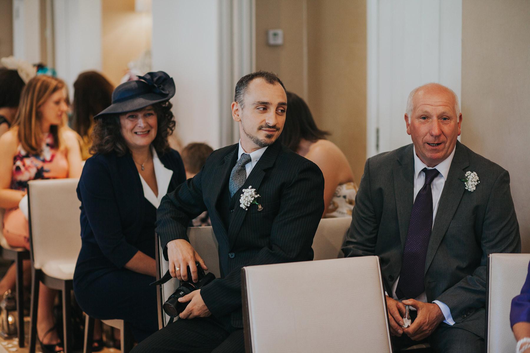 The Bingham Wedding Photographer London--groom waiting with guests ceremony room-CRL-99.jpg