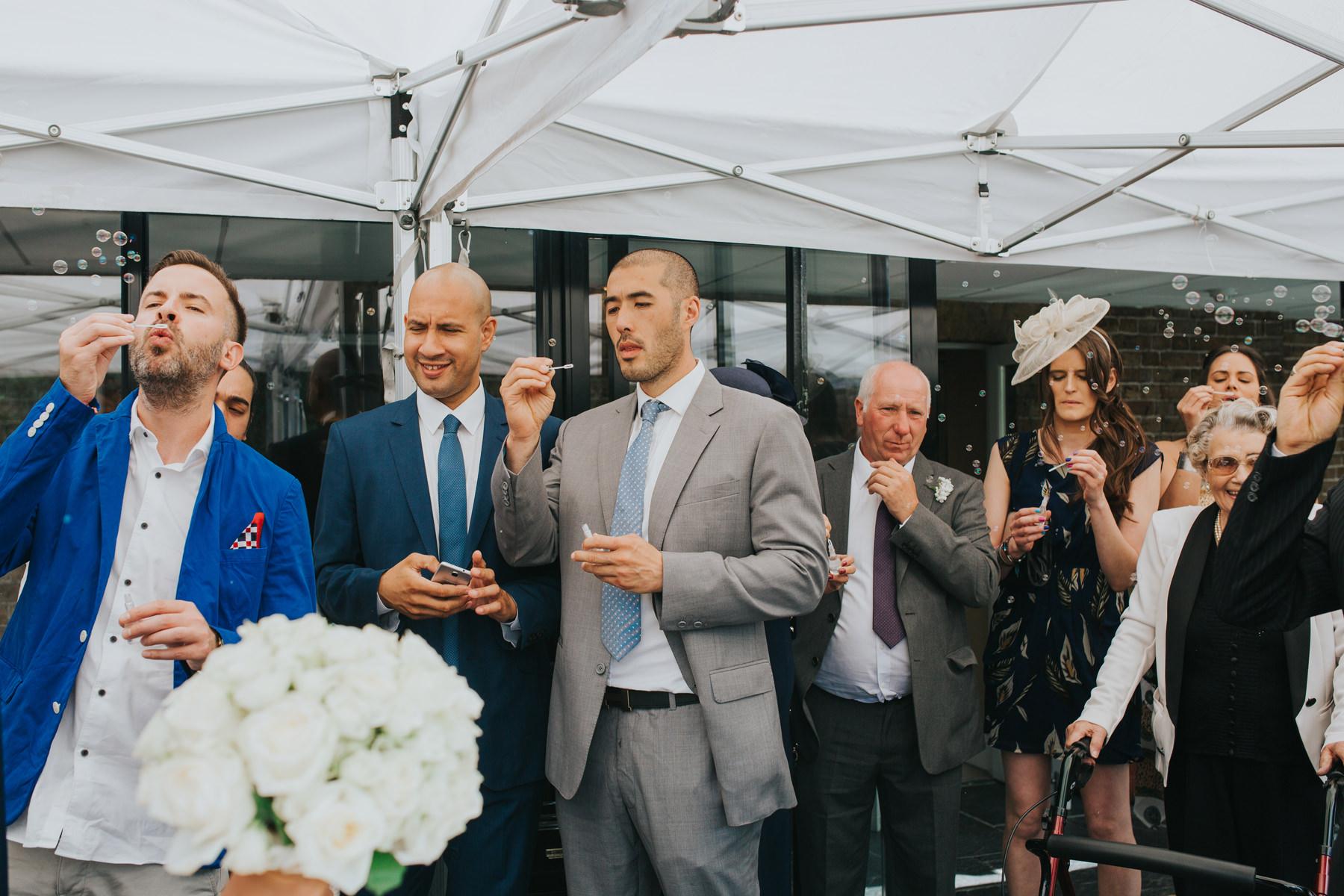 CRL-228-The Bingham Wedding Richmond-groom bride guests blowing bubbles.jpg