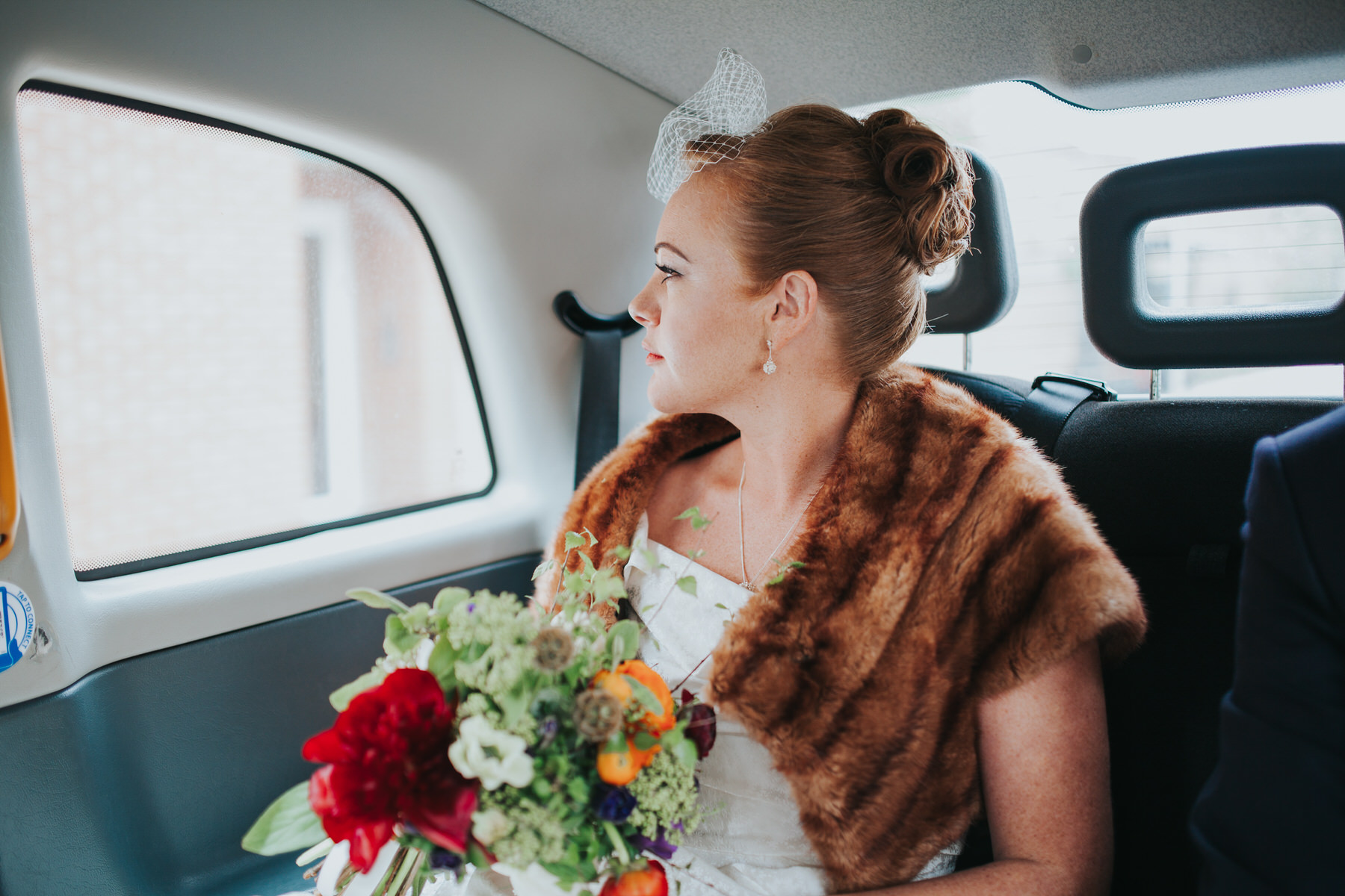 bride holding bouquet London black cab
