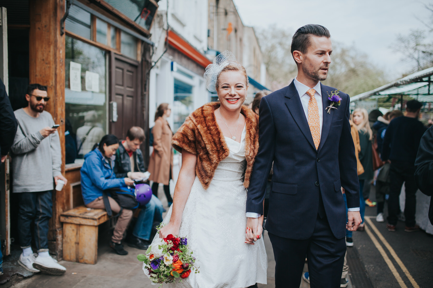 groom holding brides hand Broadway market wedding portraits