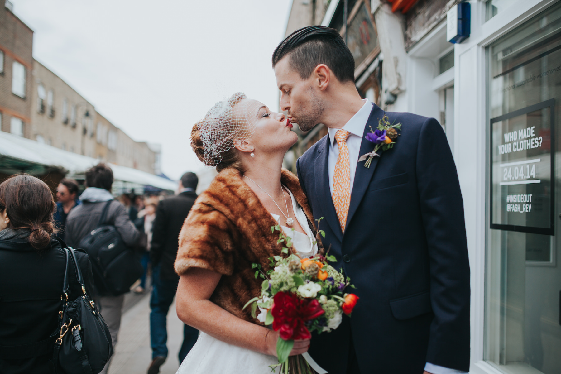 groom kissing bride quirky street portrait London