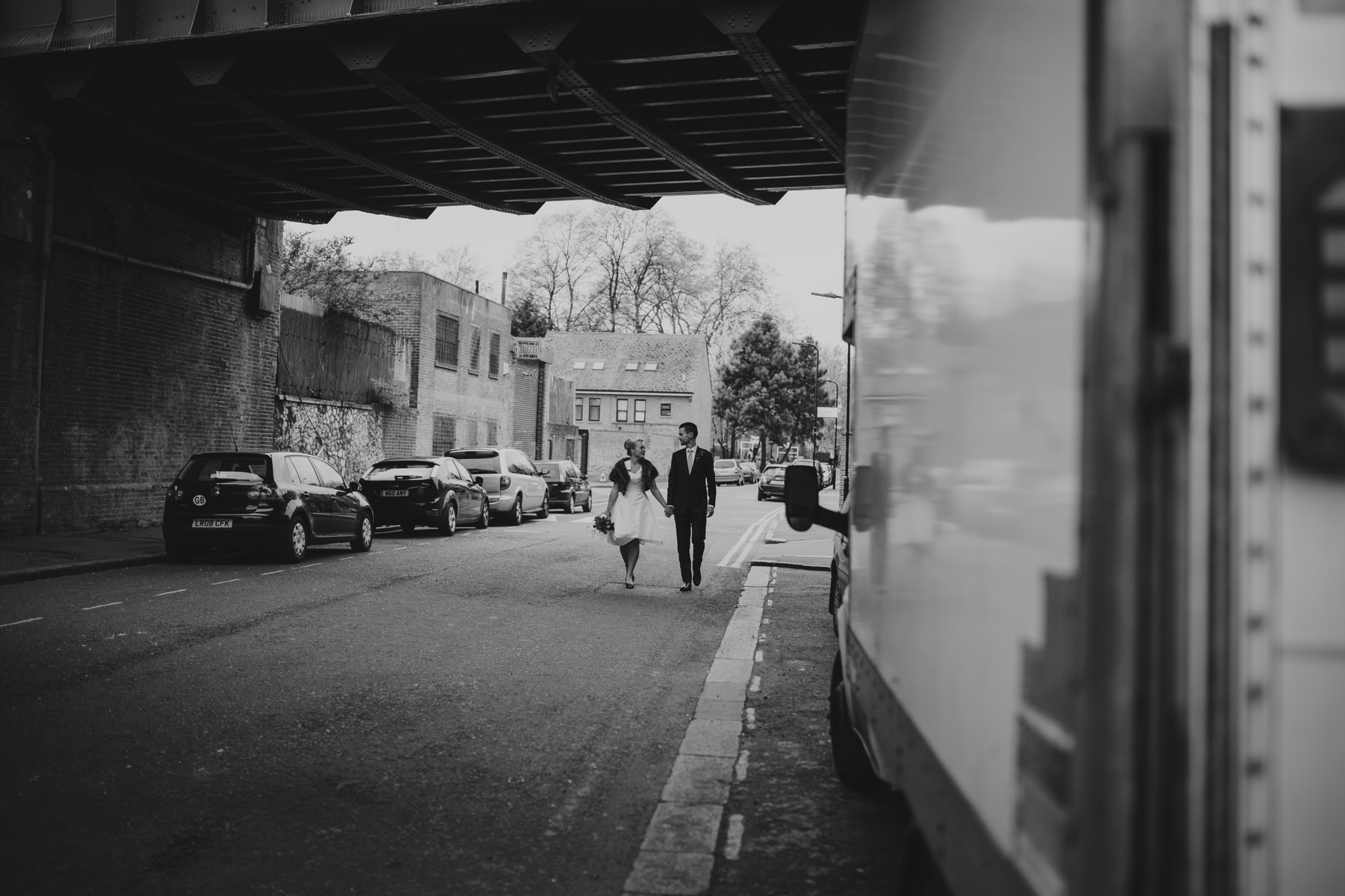 MS-Londesborough-Pub-wedding-Hackney-alternative-photographer-54-BW-bride-walking-groom-under-bridge.jpg