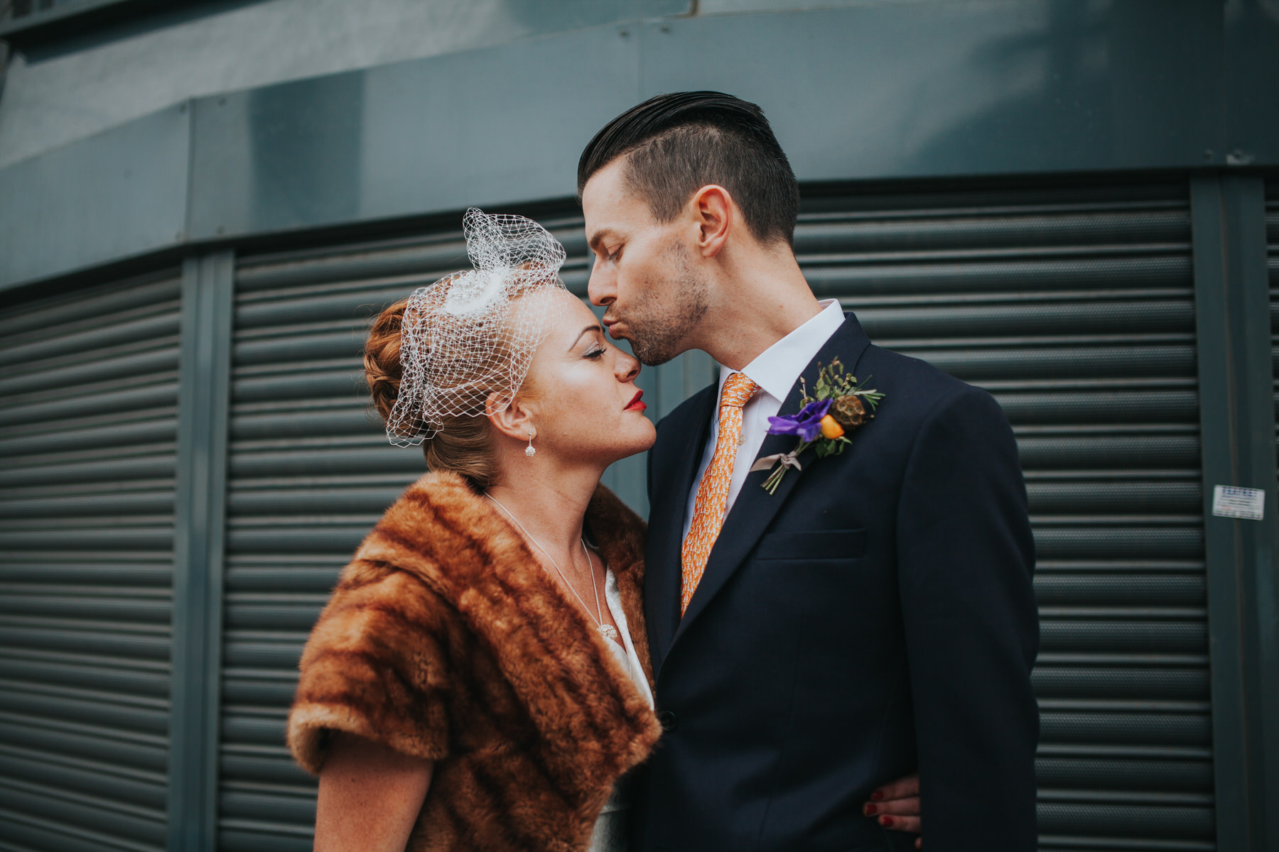 MS-Londesborough-Pub-wedding-Hackney-alternative-photographer-56-bride-wearing-fur-stole-over-wedding-dress-kissing-groom-grey-metal-background.jpg