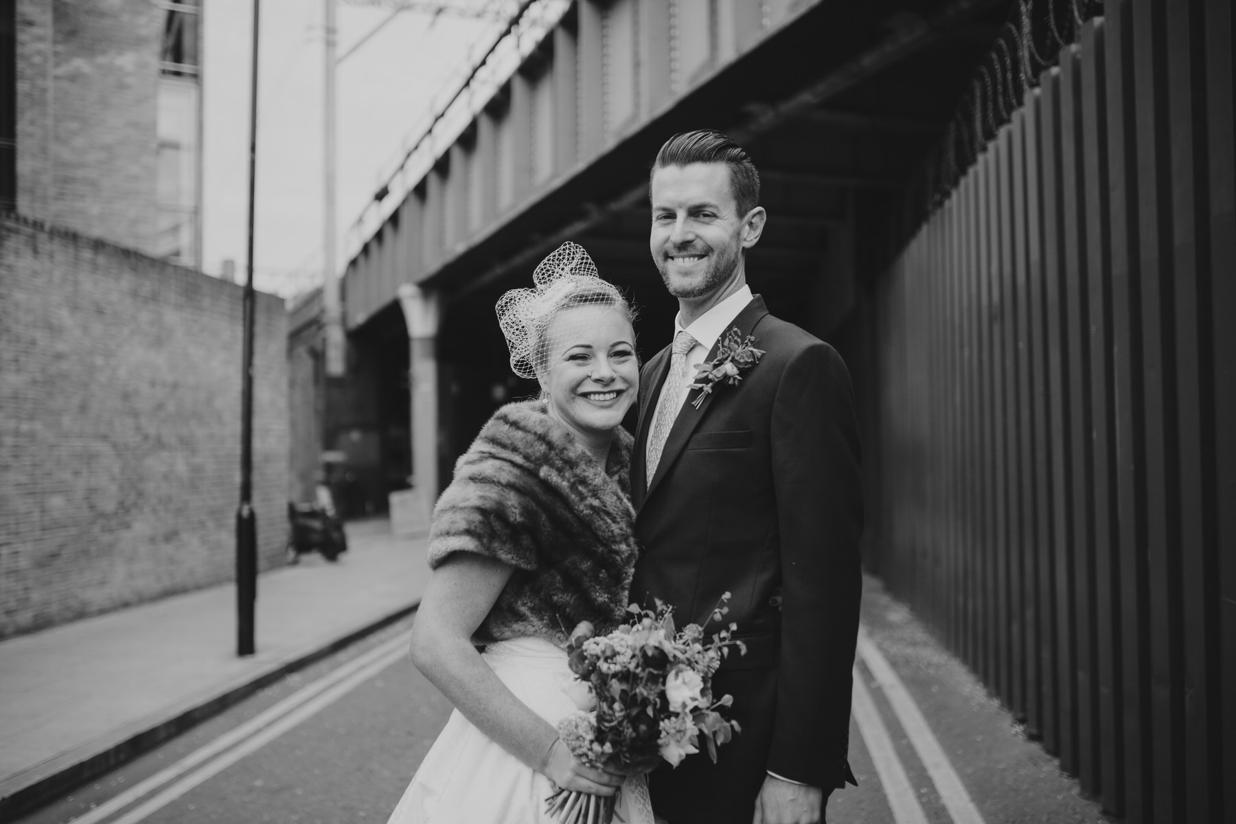 MS-Londesborough-Pub-wedding-Hackney-alternative-photographer-75-BW-urban-wedding-portrait-bride-groom-under-railway-bridge.jpg