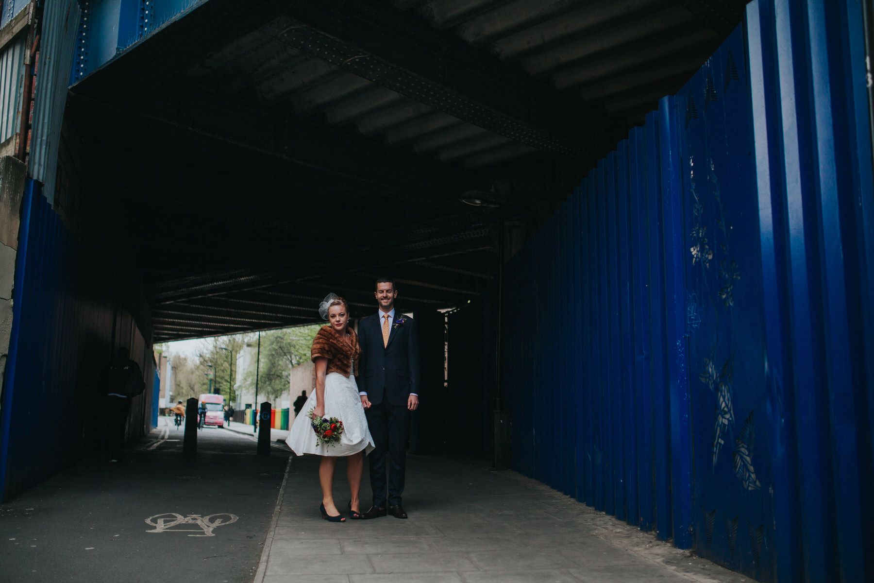 MS-Londesborough-Pub-wedding-Hackney-alternative-photographer-82-bright-blue-metal-background-urban-wedding-portrait-bride-groom-under-railway-bridge.jpg