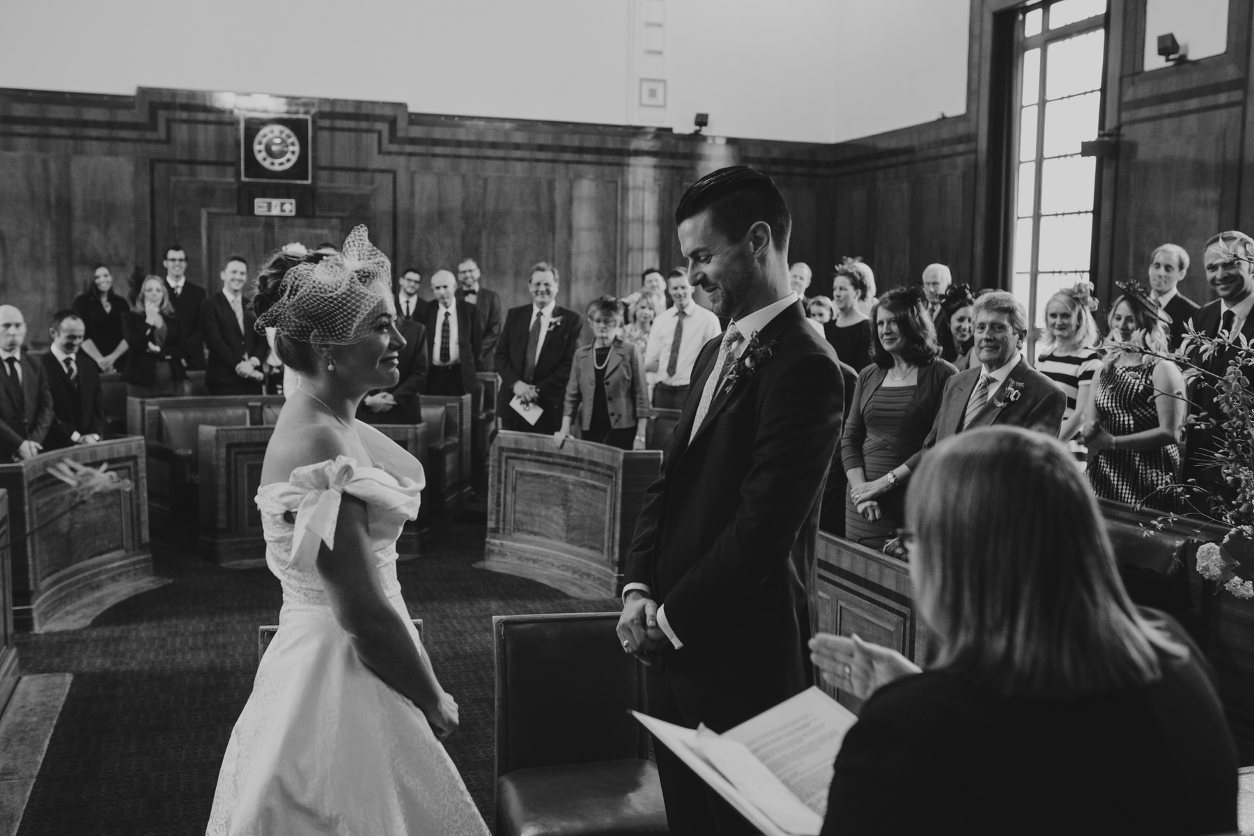 MS-Londesborough-Pub-wedding-Hackney-alternative-photographer-113-groom-laughing-during-ceremony-family-friends-BW.jpg