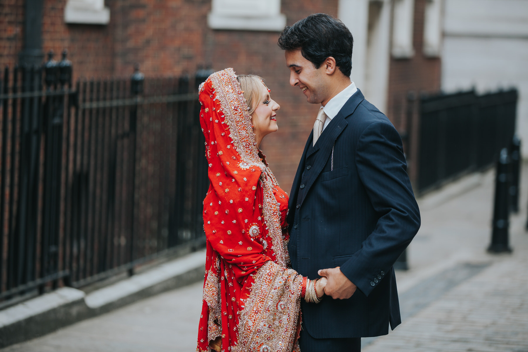 3-Anglo-Asian-London-Wedding-Middle-temple-bride-red-sari-groom-smiling.jpg