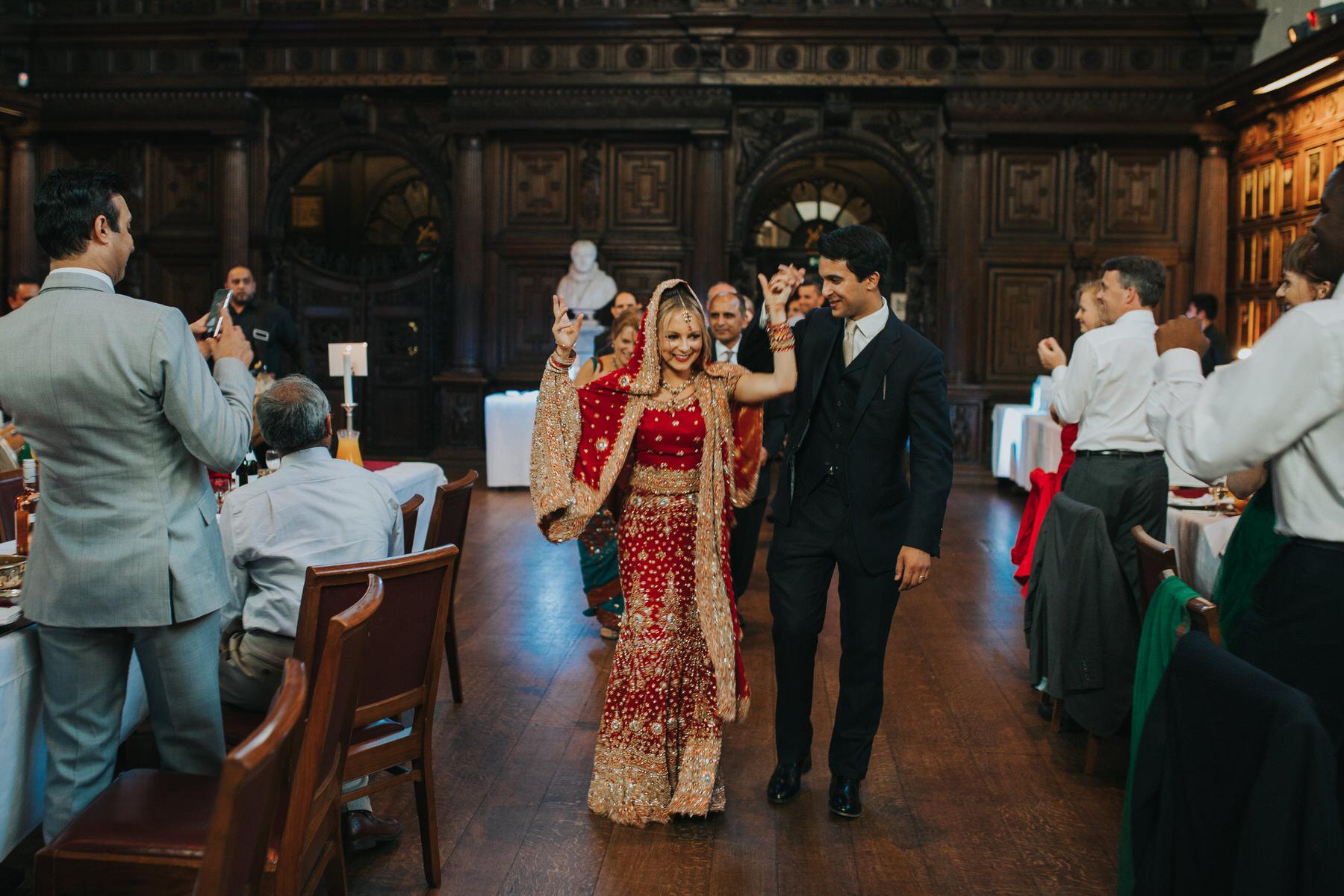 174-Anglo-Asian-wedding-groom-leads-bride-red-sari.jpg