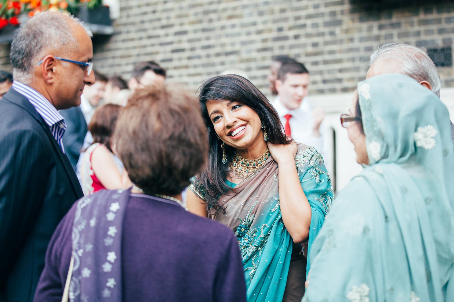 139-Anglo-Asian-London-Wedding-happy-guest-green-sari.jpg