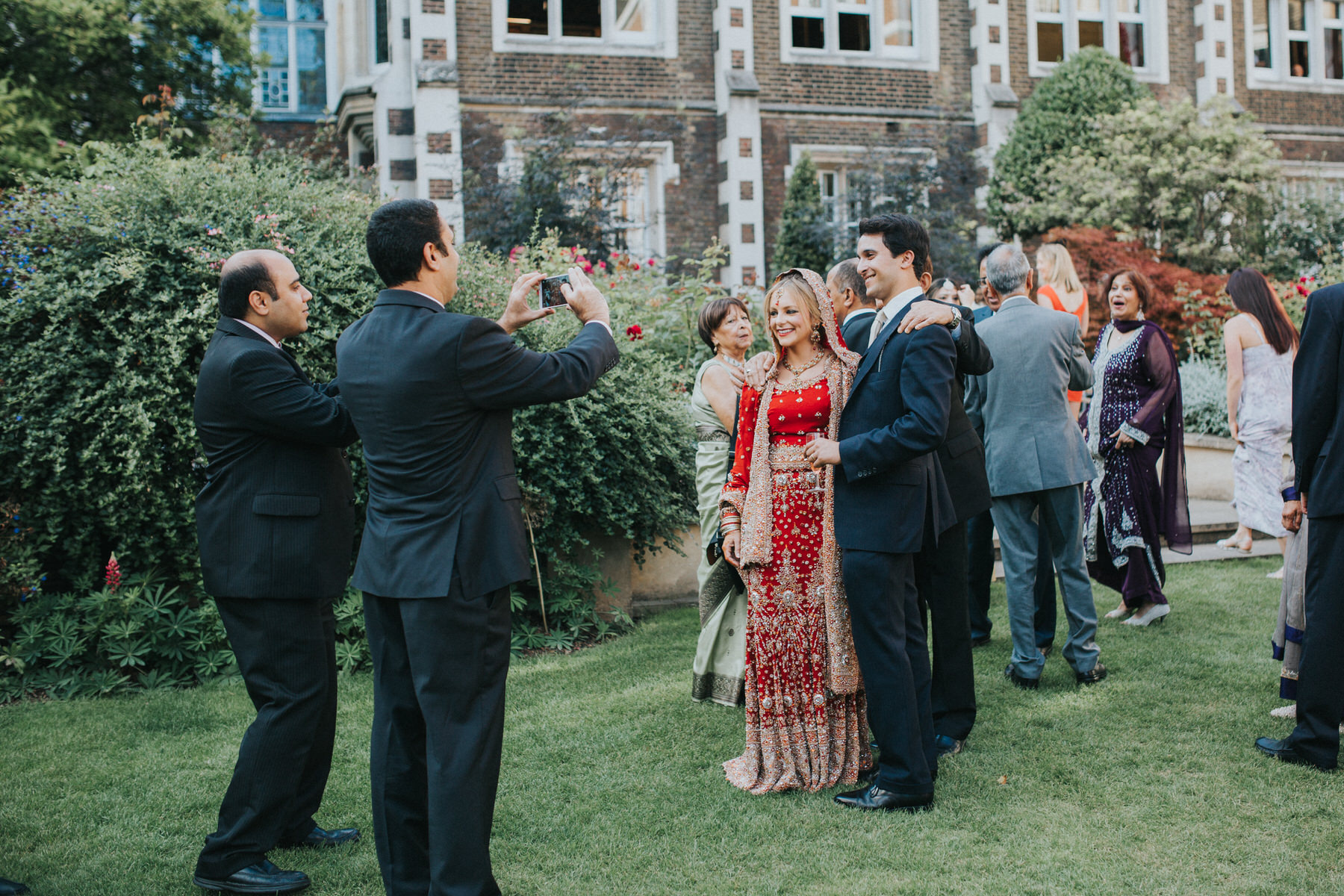155-Anglo-Asian-Wedding-guests-photographing-bride-groom.jpg