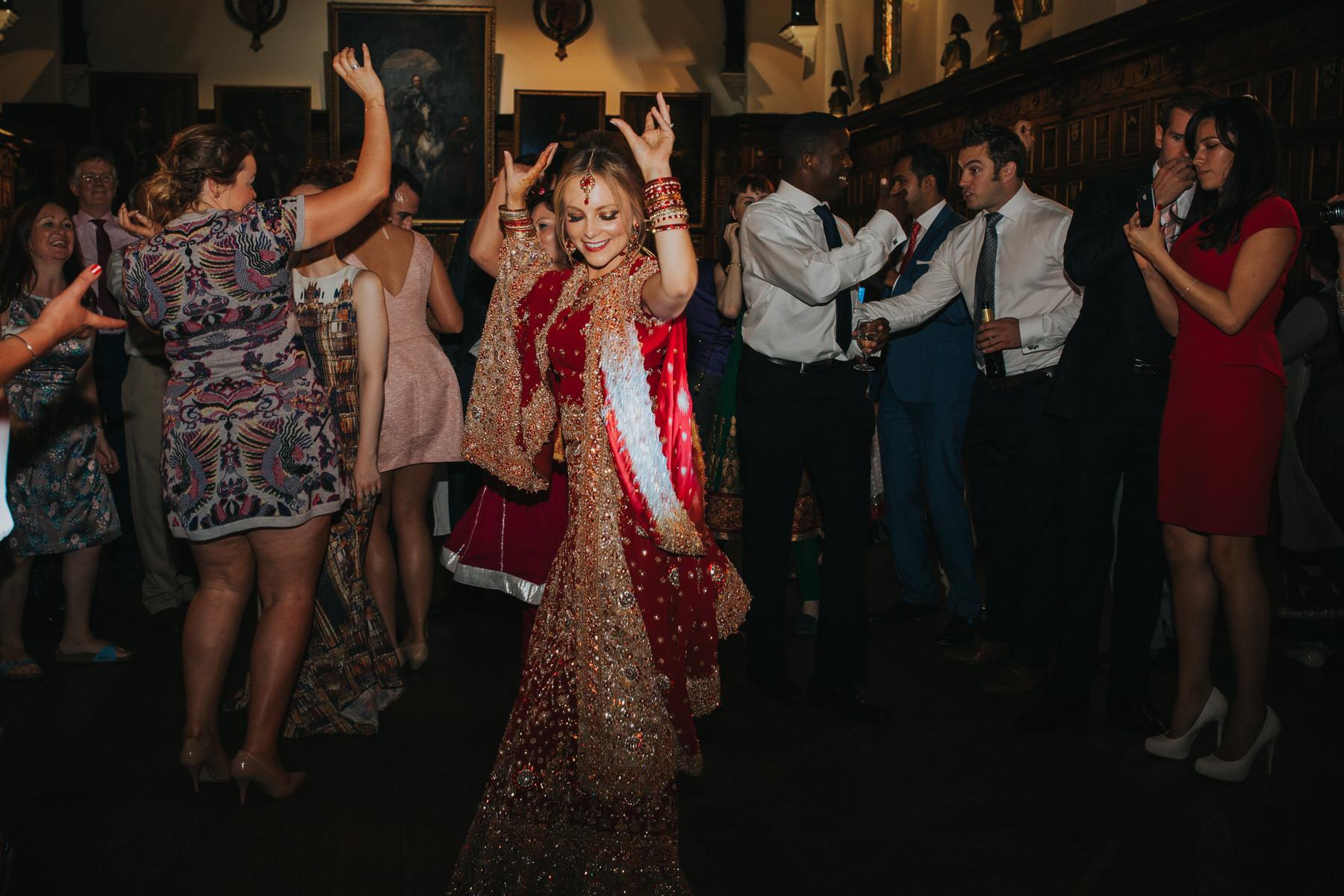 232-Anglo-Asian-wedding-bride-dancing-red-sari.jpg