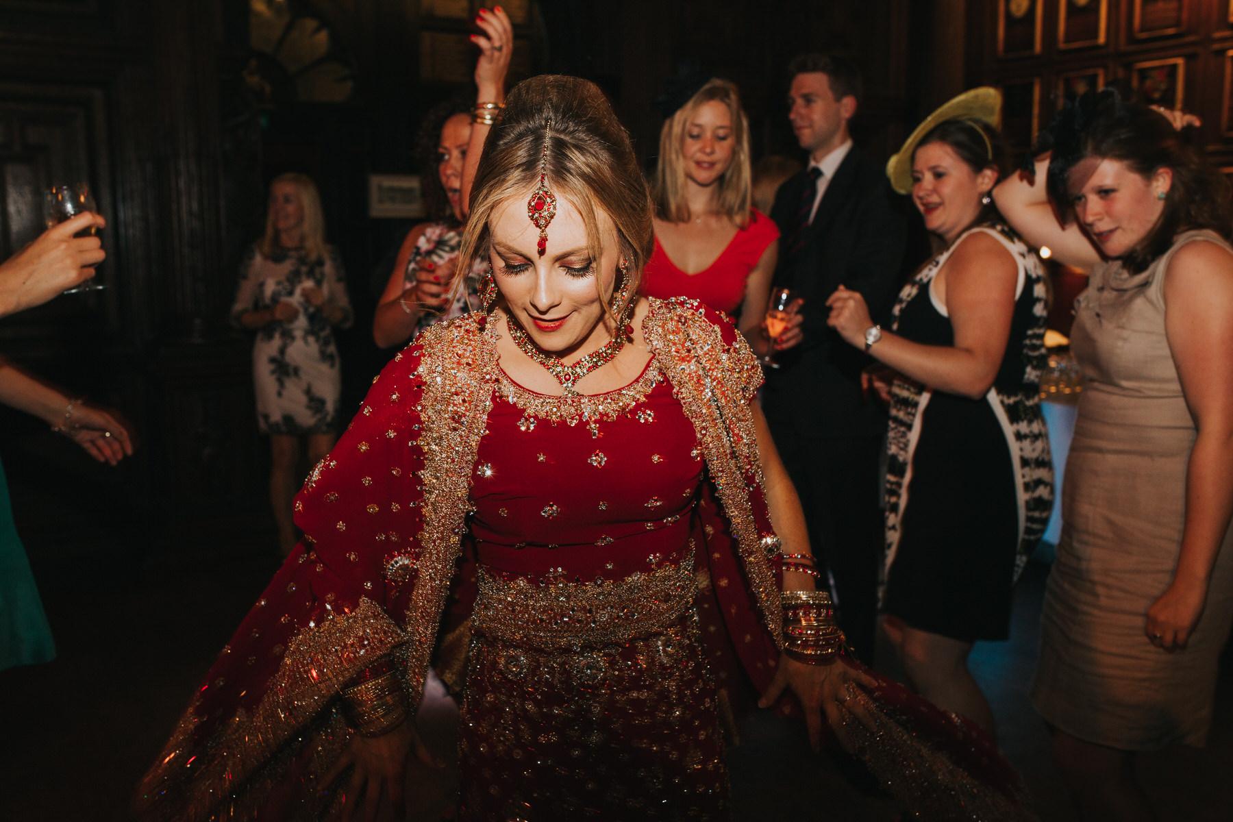 234-Anglo-Asian-wedding-bride-dancing-red-sari.jpg