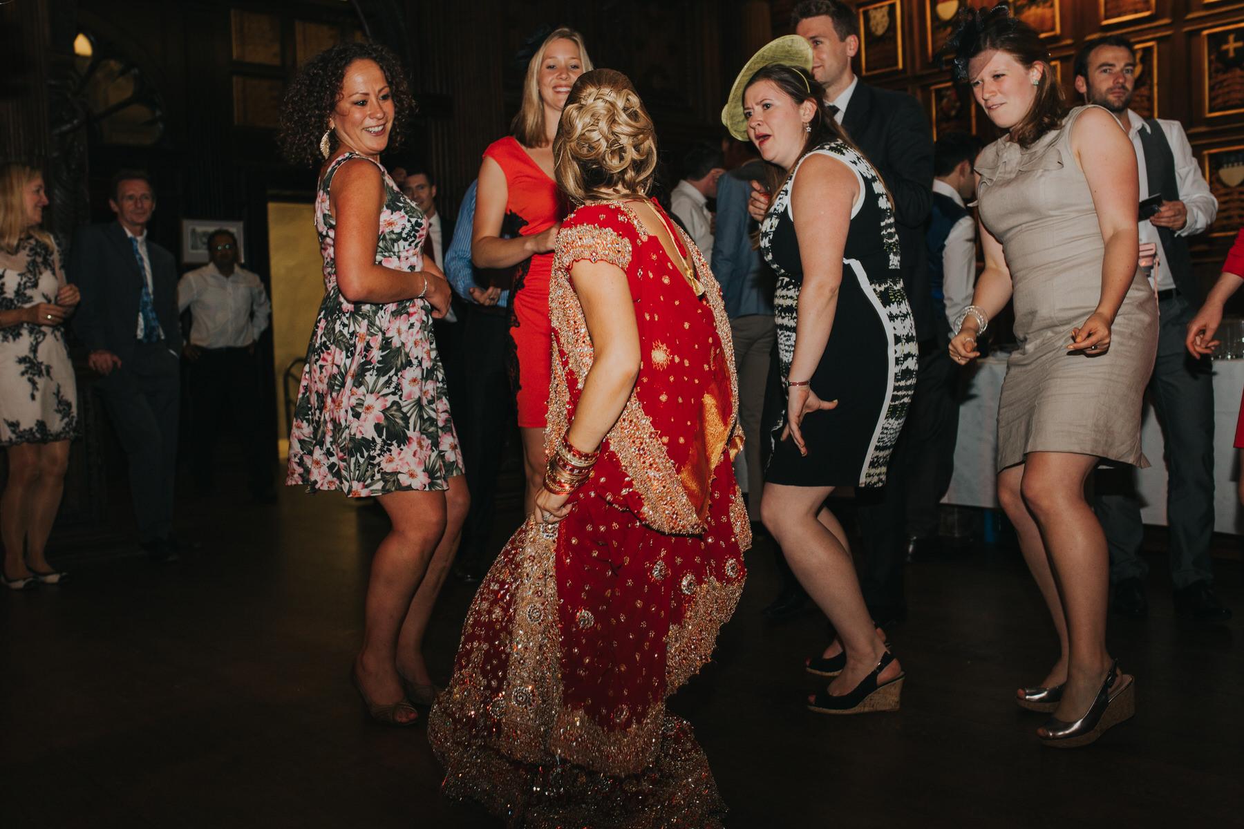 235-bride-dancing-red-sari-wedding-guests.jpg