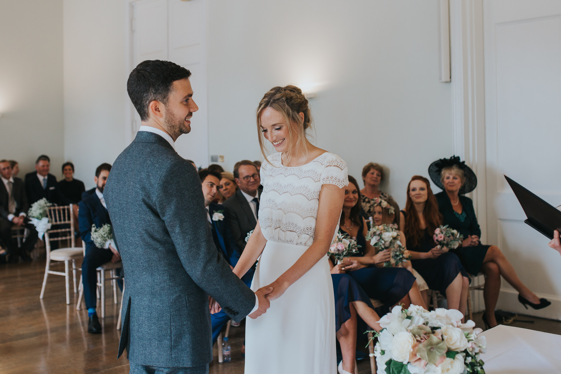 blushing bride holds hands with groom during ceremony.jpg