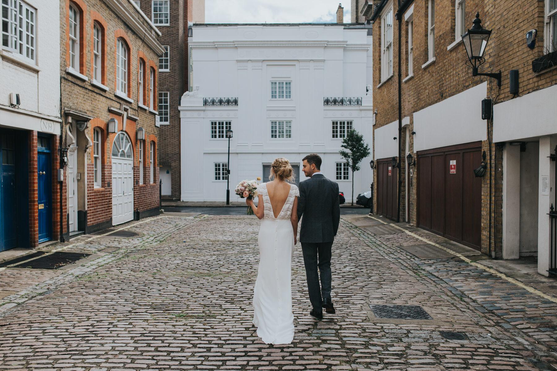 bride and groom walk away cobble mews near Asia House.jpg