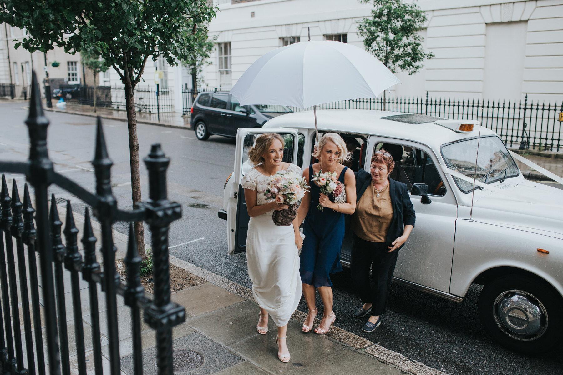 bride stepping under umbrella from wedding car Asia House.jpg