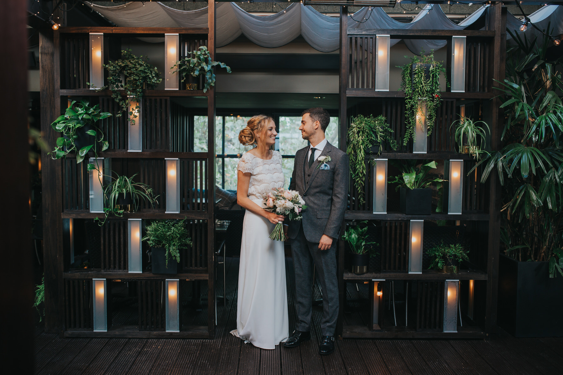 Century Club terrace bride groom poses surrounded by plants.jpg