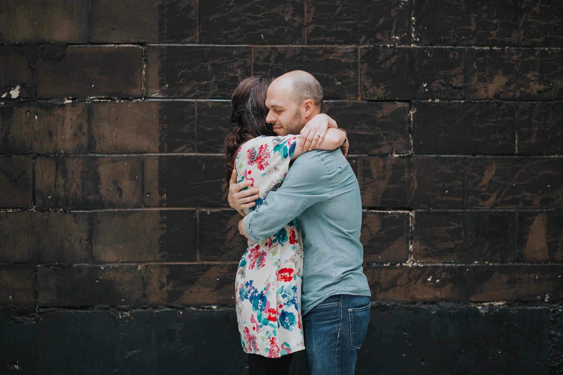 14-couple cuddling against urban background London.jpg