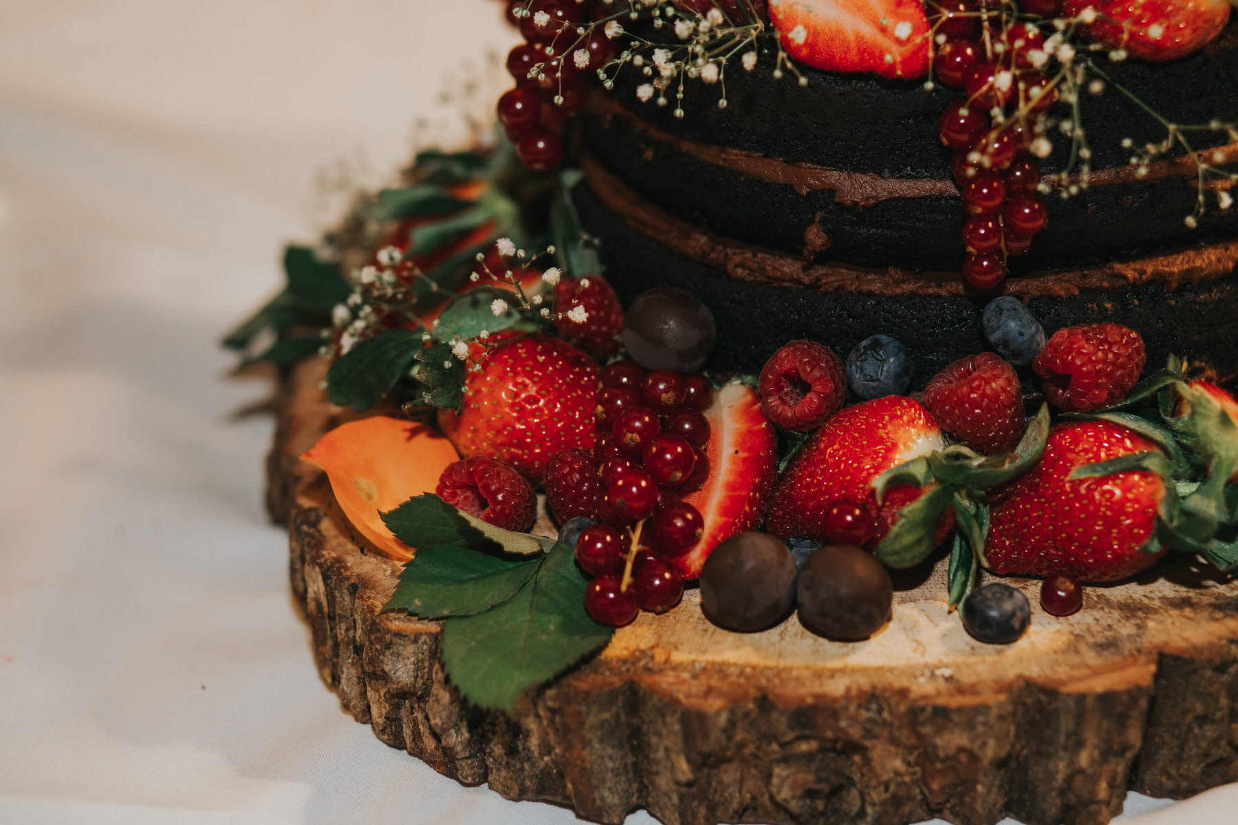 146.2-St Chads Place chocolate wedding cake decorated strawberries berries babies breath wooden board.jpg