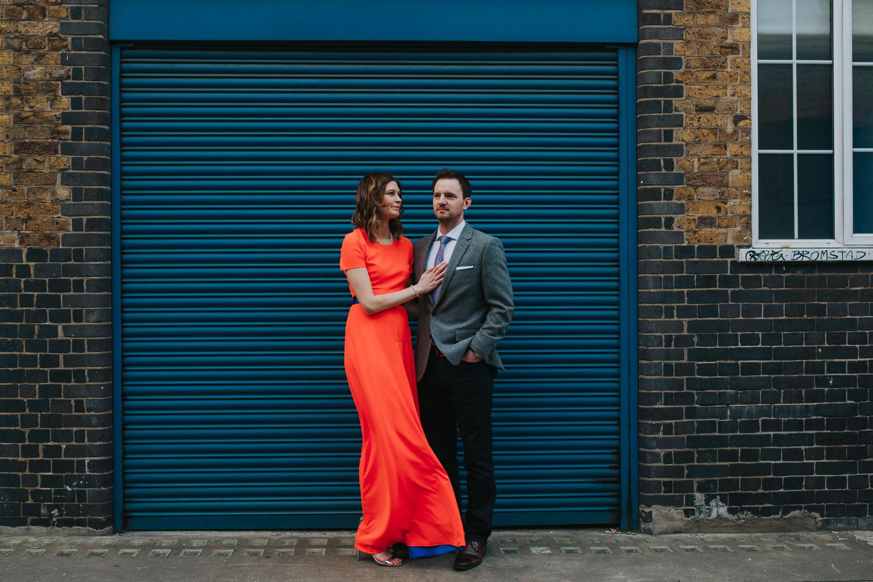 73-London wedding portraits blue metal door bride wears neon dress.jpg