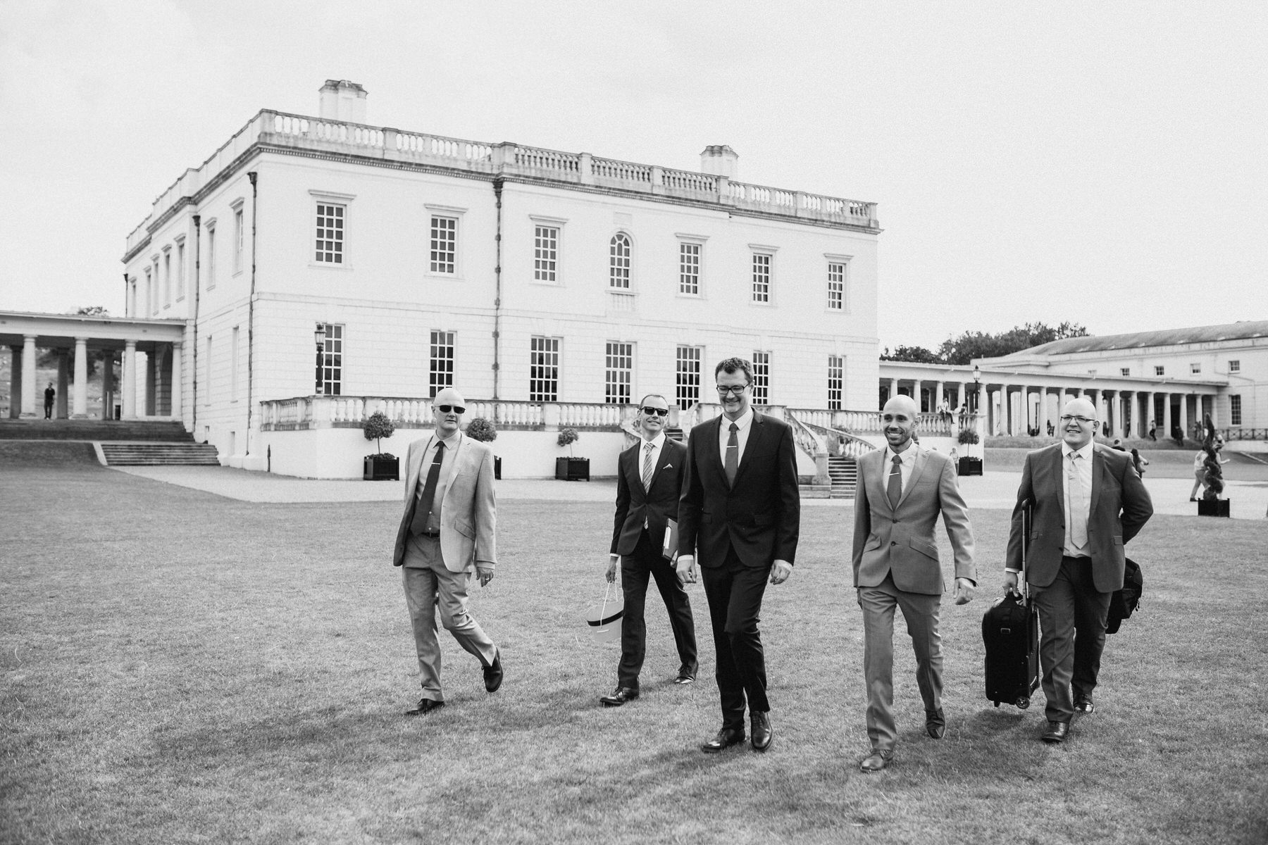 51 two grooms walking through Greenwich with wedding party BW.jpg